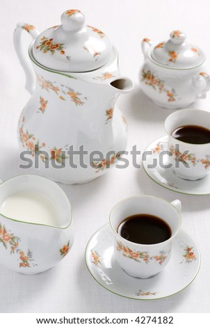 Coffee (or tea) floral pattern service - porcelain tea-kettle, two china cups, milk jug and sugar basin on the white tablecloth. Shallow DOF.