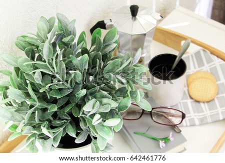 Coffee pot, cup of coffee, the book is on a tray #642461776