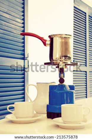 Coffee pot on a primus stove with cups and jug on summer veranda. Coffee concept.