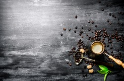 Coffee pot with coffee beans, cane sugar and fresh leaves. On a black chalkboard.