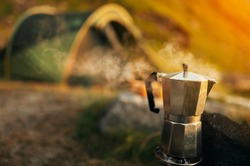Coffee pot with steam in front of Camp with tent in Lofoten islands, Northern Norway, Kvalvika beach, during sunset.