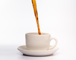 Coffee pouring into a plain white cup and saucer