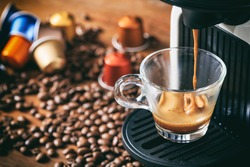 Coffee preparation. Espresso coffee maker machine and capsules on a wooden table, closeup view