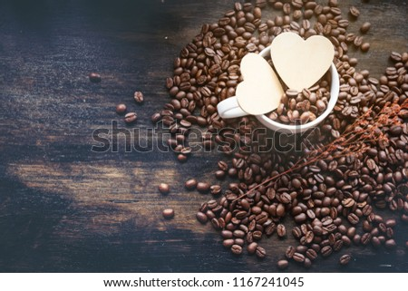 Coffee's bean in white cup of coffee and wooden cartoon heart in cup. prepare to grind and brew hot coffee.  #1167241045