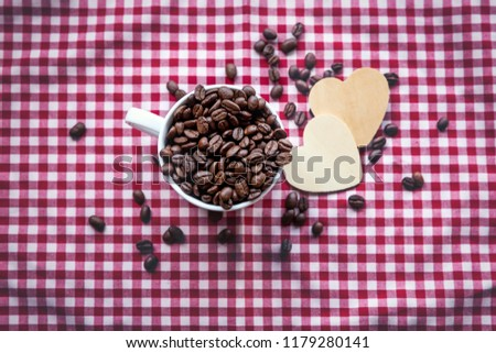 Coffee's bean in white cup of coffee and wooden cartoon heart in cup. prepare to grind and brew hot coffee. all put on white and red table cloth. #1179280141