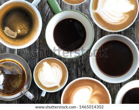 Coffee set in white glass, placed on an old wooden table top.Coffee cup assortment top view collection.Many cups of coffee on wooden table.Different cups of coffee on wooden table.Top view.