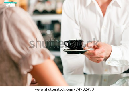 Coffee shop - barista in cafe waits a coffee to a client