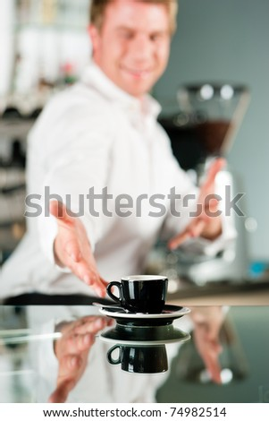 Coffee shop - barista presents coffee in his cafe