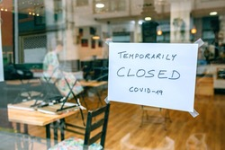 Coffee shop closed by covid-19 with workers picking up and cleaning inside