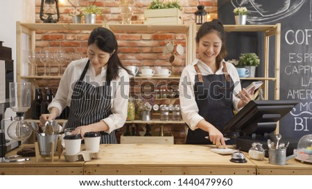 coffee shop co-workers standing together in counter. two waitresses chatting while working in cafe bar. female barista laughing with gossip during make latte and check client order on tablet.
