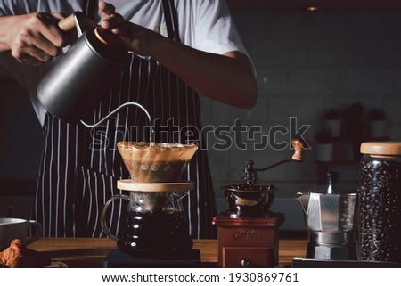 Coffee shop concept : Professional barista preparing coffee using chemex pour over coffee maker and drip kettle. Alternative ways of brewing coffee.