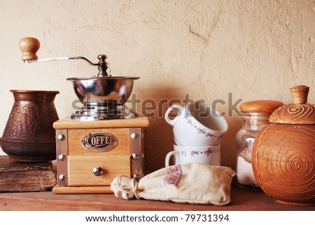 coffee still life (grinder, cup, a turk, a bag of beans, a jar) against the background of an old wall