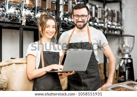 Coffee store owners or managers working with laptop standing at the counter of the shop #1058551931