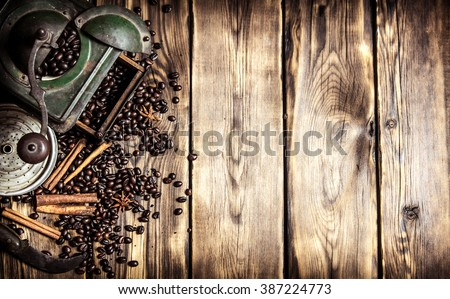 Coffee style. Old coffee grinder with coffee beans. On wooden background. #387224773