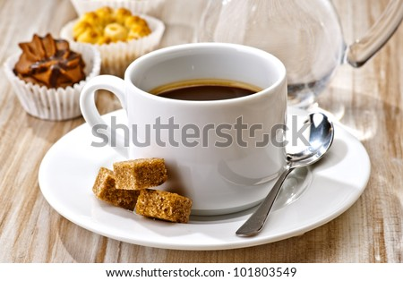 coffee, sugar, water and cakes on wooden board textured
