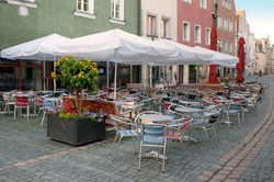 Coffee tables with umbrellas near cafe on European street, Weiden, Bavaria, Germany