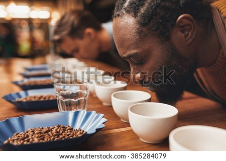 Coffee tasting with baristas smelling the aroma of many cups