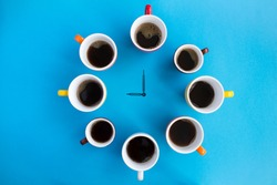 Coffee time. Composition with black coffee in bright cups and clock hands in the center of the blue  background. Top view. Copy space.