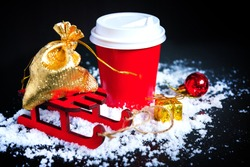 Coffee to go in red paper cup, sledge, golden sack and christmas present on black background. Hot drinks in cold winter. New Year and Christmas.