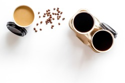 Coffee to take away in paper cups with beans on white table background top view space for text