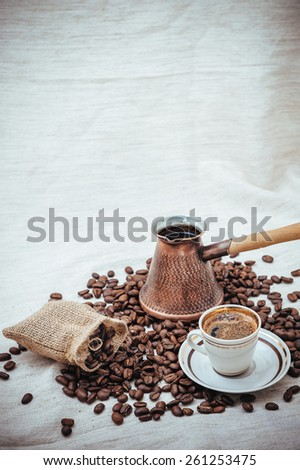 Coffee turk and cup of coffee on burlap background. coffee beans isolated on white background. roasted coffee beans