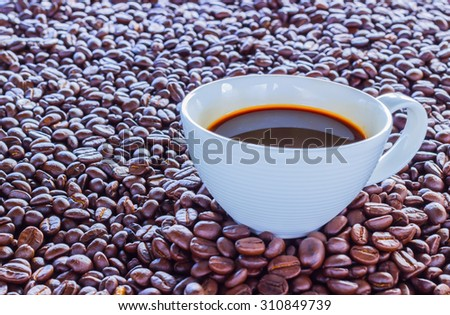 Coffee wallpaper, background, grains of coffee plant and black coffee drink in white coffee set. Coffee time texture.