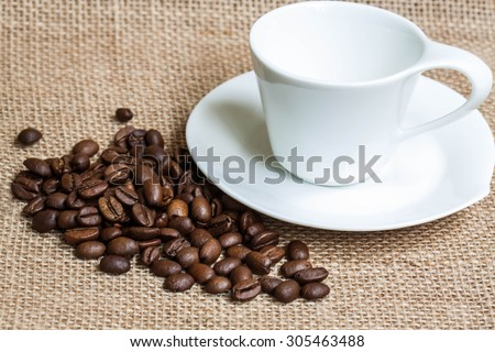Coffee  wallpaper, background, grains of coffee plant and  white coffee set  on  burlap, sackcloth texture.