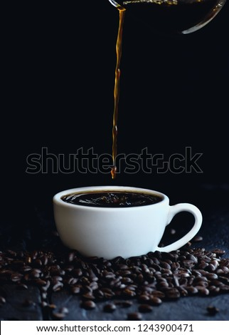 Coffee​ water​ drop to​ the​ white​ color​ coffee​ cup​ with​ coffee​ beans  on​ the​ ground in​ dark  color​ tone.selective focus the​ coffee​ cup.