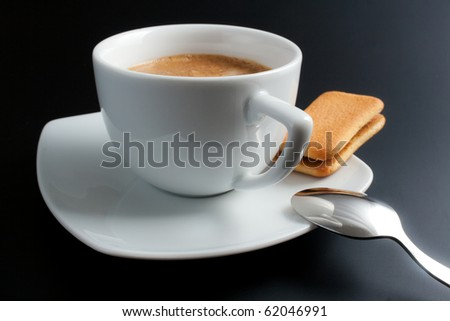 Coffee. White porcelain cup of freshly brewed coffee close-up arranged with sandwich-biscuit spoon and plate on dark background