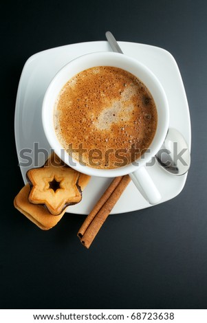 Coffee. White porcelain cup of freshly brewed coffee top view close-up arranged with two sandwich-biscuits, cinnamon stick, spoon and plate on dark background