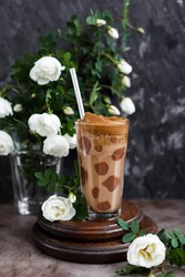 Coffee with chocolate and whipped foam in a transparent glass with a straw on a table with white roses. Unusual design of a coffee drink.