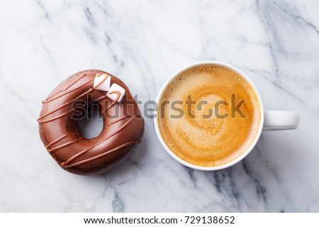 Coffee with chocolate donut in marble table background. Top view.