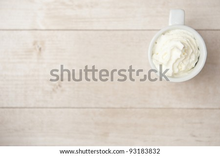 Coffee with cream over a wood table - stock photo