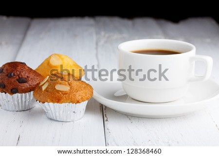 Coffee with cupcakes on wooden table