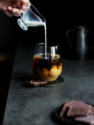 Coffee with milk in glass at dark background. Hand pouring milk cream in cold coffee. Concept of tasty refreshment beverage with coffee. Copy space for text, menu or recipe