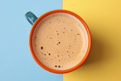 coffee with milk top view on yellow and blue backdrop