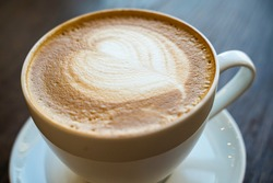 coffee with vegetable milk with foam on a wooden background