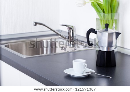 Coffeemaker and cup of coffee in kitchen interior