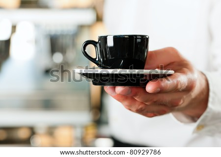 Coffeeshop - barista presents coffee or cappuccino; close-up on mug