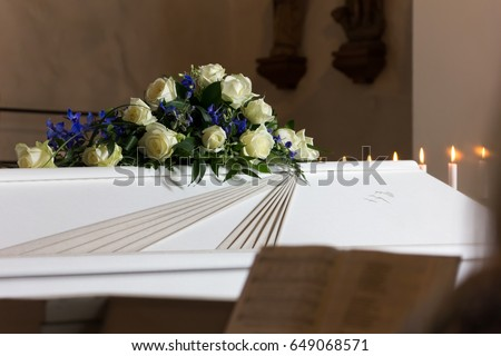 Coffin with a flower wreath in the church at a funeral