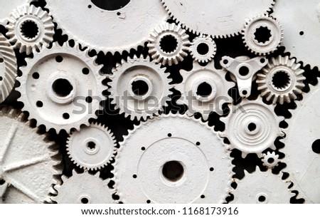 Cog wheels, old gears painted in white. Engine gear wheels, industrial background