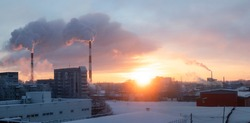 Cogeneration or combined heat and power station in outskirts of town in frosty winter day. Fume from pipes in the sunset sky.