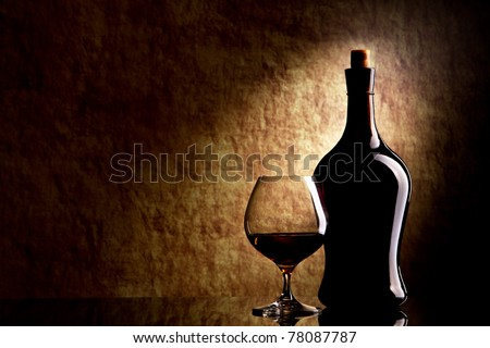 Cognac Glass and Bottle on a old stone background
