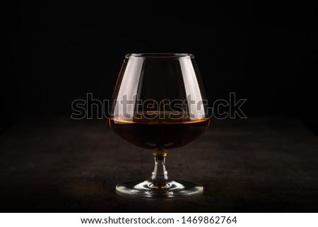 Cognac or brandy in the glass. Dark background. #1469862764