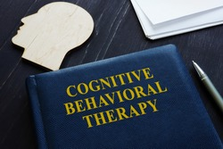 Cognitive behavioral therapy CBT book and wooden head shape.