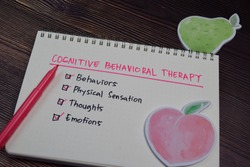 Cognitive Behavioral Therapy write on a book with keywords isolated wooden table.