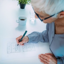 Cognitive training. Senior woman solving sudoku puzzles.