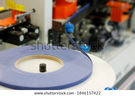 Coil of edge banding tape on a feed support plate of automatic edge bander. Selective focus. Zdjęcia stock ©