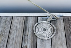 coil of rope on weathered wood deck tied onto a cleat