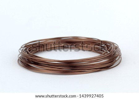 Coil of wire with a hint of copper, bronze on a light background. #1439927405